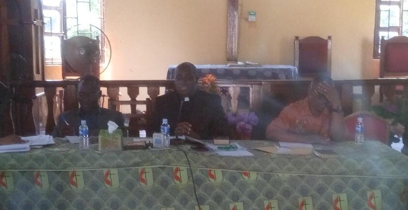 Le révérend Raphaël Nogbou en noir à la table de séance